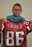 student with jersey after meeting Dj Tialavea of the Atlanta Falcons speaking at West Jordan School